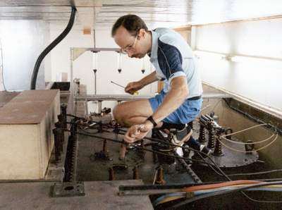 FEBCanada missionary Mark Fuller working on a transmitter in the Seychelles. (1988)